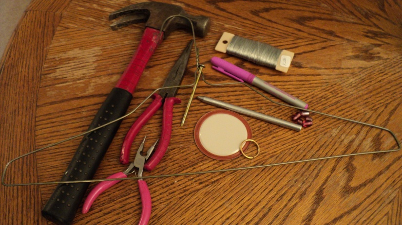 Hammer, wire cutters, etching pen, wire hanger, used canning lid, etching pen, permanent marker, wire, jump ring(s) and beads.